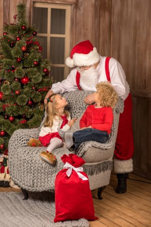 Photo for Happy children sitting on grey armchair and looking at Santa Claus - Royalty Free Image