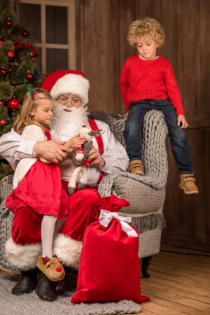 Photo for Santa Claus sitting on grey armchair with happy children - Royalty Free Image
