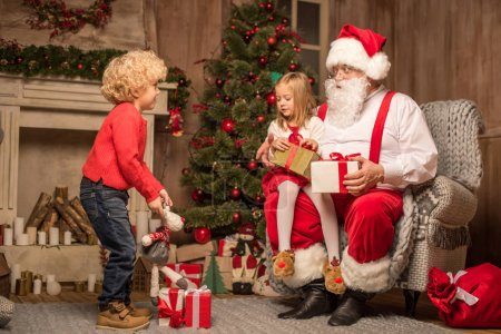 Photo for Santa Claus sitting with happy children and looking their gift boxes - Royalty Free Image