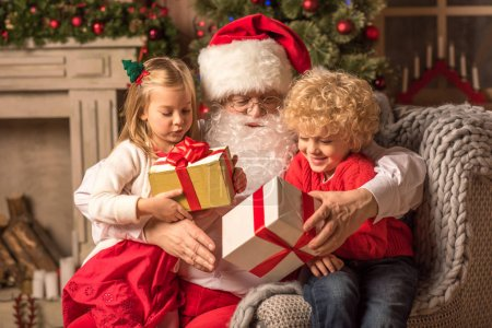 Photo for Happy Santa Claus with children holding gift boxes - Royalty Free Image