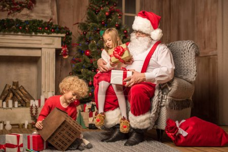 Photo for Santa Claus with children sitting near fireplace and looking at gift boxes - Royalty Free Image