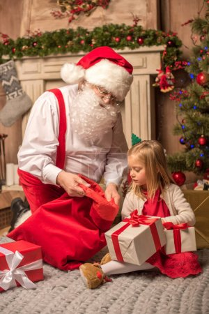 Photo for Santa Claus showing Christmas presents to little kid - Royalty Free Image