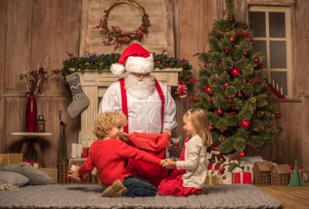 Photo for Santa Claus showing Christmas presents from red sack to children - Royalty Free Image