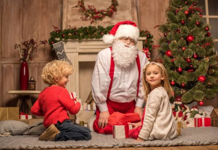 Photo for Happy Santa Claus and children sitting on carpet with Christmas gifts - Royalty Free Image