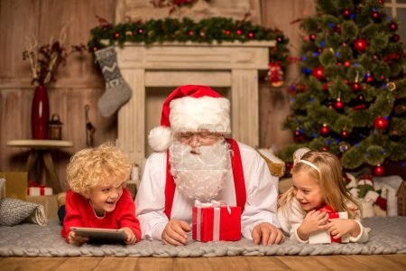 Photo for Happy Santa Claus and children lying on carpet with Christmas gifts - Royalty Free Image