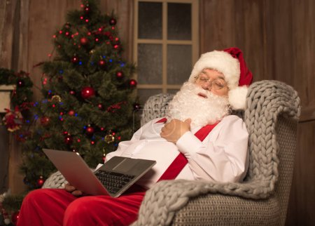 Photo for Sleeping Santa Claus on grey armchair with laptop on knees - Royalty Free Image
