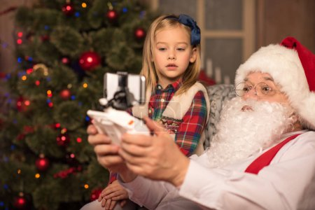 Photo for Portrait of Santa Claus with little kid sitting together - Royalty Free Image