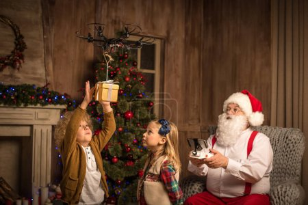 Photo for Santa Claus using hexacopter drone while children looking at flying gift box - Royalty Free Image