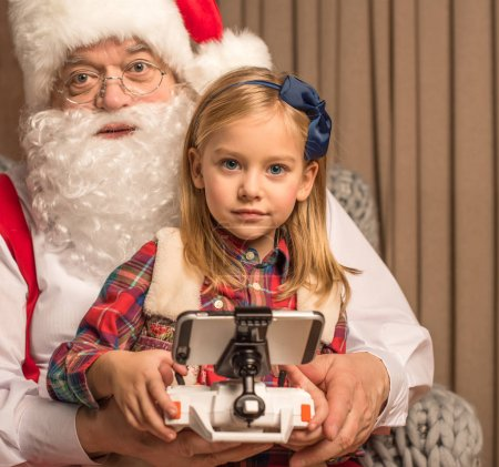 Santa Claus with kid looking at camera