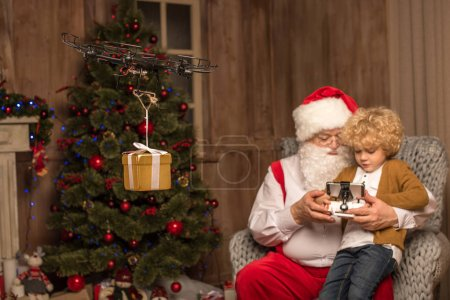 Photo for Santa sitting on grey armchair with kid and using hexacopter drone - Royalty Free Image