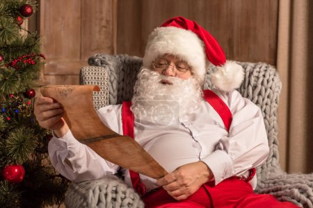 Photo for Santa Claus sitting in grey armchair and reading wishlist - Royalty Free Image