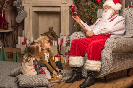 Photo for Santa Claus reading wishlist and children looking at him - Royalty Free Image