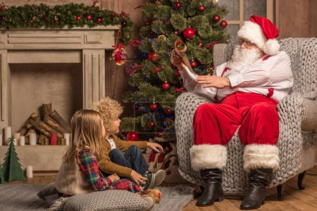 Photo for Santa Claus reading wishlist while children sitting on carpet - Royalty Free Image