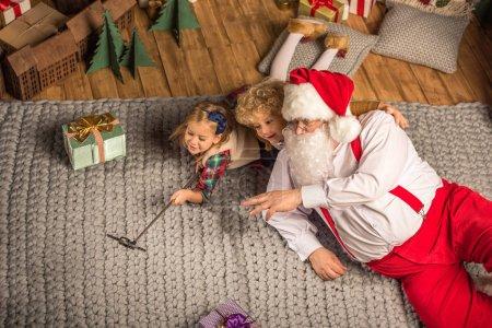 Santa Claus with children taking selfie