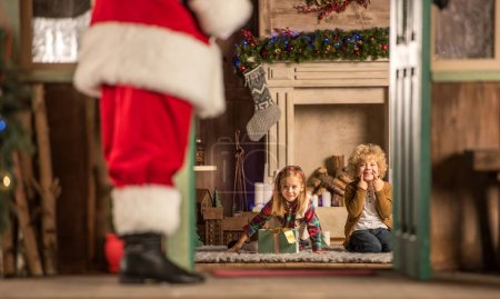 Photo for Children sitting near fireplace and waiting for Santa Claus - Royalty Free Image