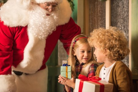 Photo for Santa Claus with children holding gift boxes - Royalty Free Image