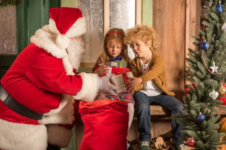 Photo for Santa Claus giving gift boxes to children from sack - Royalty Free Image
