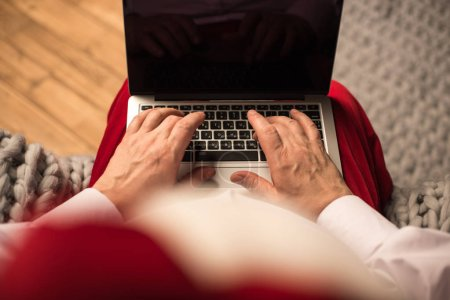 Santa Claus typing on laptop