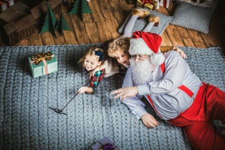 Photo for Happy Santa Claus with children lying on carpet and taking selfie - Royalty Free Image