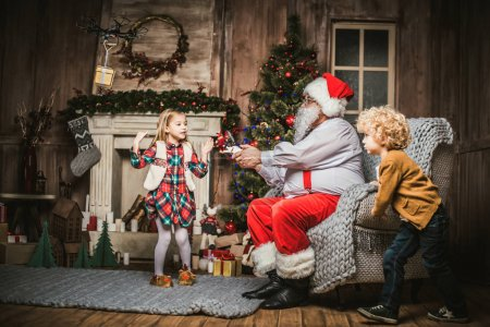 Photo for Santa Claus with children using hexacopter drone - Royalty Free Image