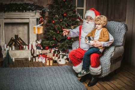 Photo for Santa with kid sitting on armchair and using hexacopter drone - Royalty Free Image