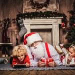 Happy Santa Claus lying on grey carpet with children