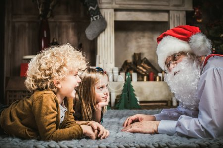 Photo for Happy Santa Claus lying on grey carpet with children - Royalty Free Image