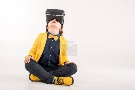 Photo pour Enfant en réalité virtuelle casque assis sur gris - image libre de droit