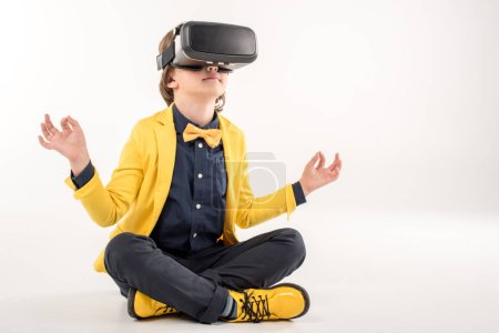 Photo for Kid in virtual reality headset sitting on grey - Royalty Free Image