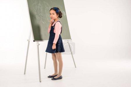 Schoolgirl standing near chalkboard