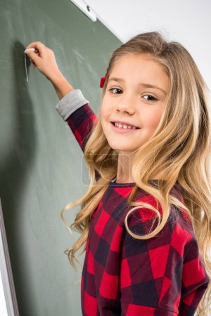 Photo for Smiling schoolgirl writing with chalk on blackboard - Royalty Free Image