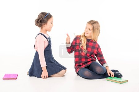 Schoolgirls with books gesturing