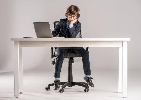 Photo pour Écolier en tailleur assis sur le Bureau lors de l'utilisation d'ordinateur portable avec la main sur le menton - image libre de droit