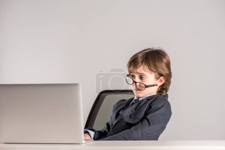 Schoolchild in business suit looking at laptop