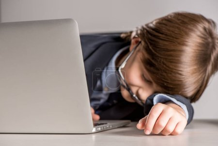 schoolchild in business suit sleeping on desk