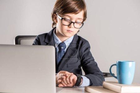 Schulkind im Businessanzug schaut auf Smartwatch
