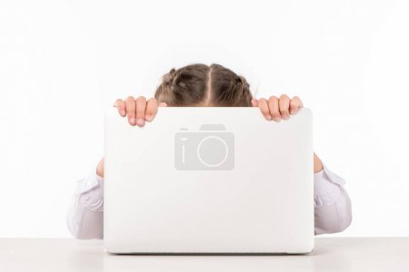 Schoolgirl hiding behind laptop