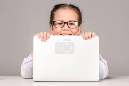 Photo pour Écolière dans des lunettes tenant ordinateur portable sur gris - image libre de droit