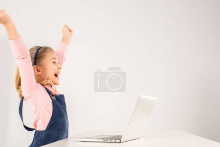 Photo for Cheerful schoolgirl sitting at desk with laptop - Royalty Free Image