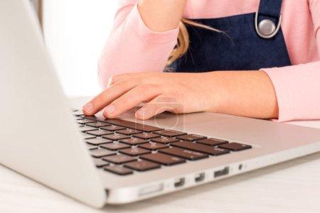 Schoolgirl at desk with laptop