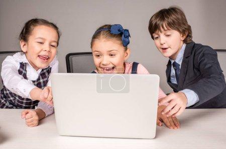 Photo pour Des camarades de classe souriants assis au bureau et utilisant un ordinateur portable - image libre de droit