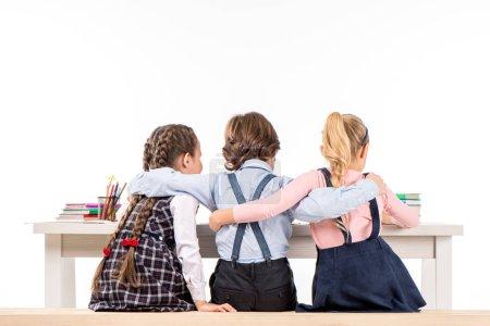 Photo pour Vue arrière des camarades de classe assis au bureau avec des livres et câlins - image libre de droit