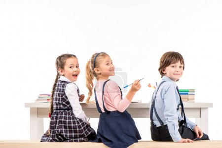 Photo for Smiling schoolchildren sitting at desk with books on white - Royalty Free Image