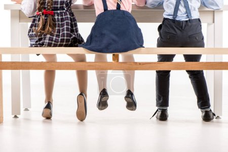 Photo for Low section of schoolchildren sitting and studying at desk - Royalty Free Image
