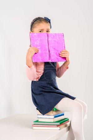 Schoolgirl sitting on pile of books