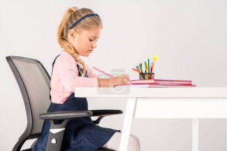 Photo for Serious schoolgirl sitting at desk and doing homework - Royalty Free Image