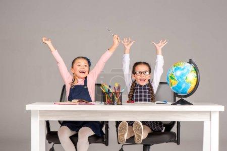 Photo pour Joyeux écolières assis avec les mains levées pendant la leçon de géographie - image libre de droit