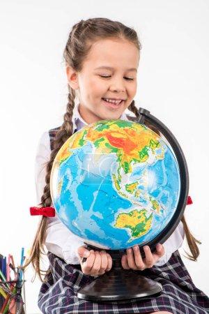 Happy schoolgirl holding globe