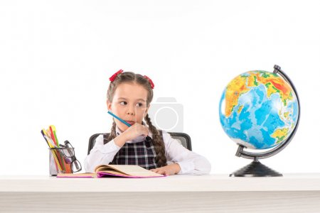 Photo for Schoolgirl doing homework and looking at globe - Royalty Free Image