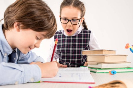 Schoolgirl looking at classmate's notebook